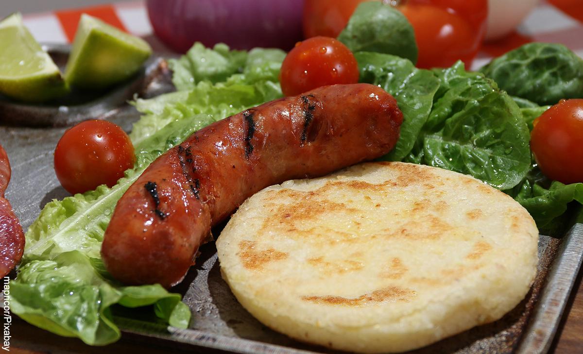 Foto de una arepa con chorizo y ensalada que muestra cómo hacer para que las arepas no queden duras