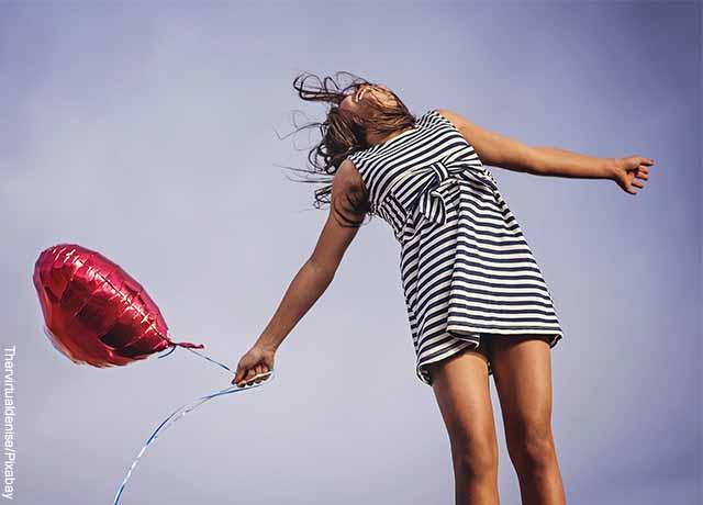 Foto de una mujer feliz abriendo sus brazos y sosteniendo un globo