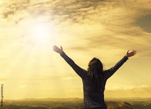 Foto de una mujer de espaldas abriendo sus brazos al amanecer