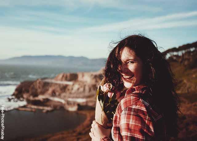 Foto de una mujer sosteniendo unas flores mientras sonríe en una colina