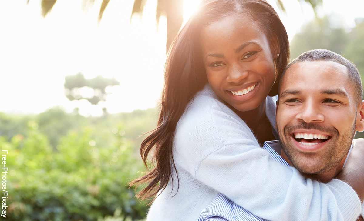 Foto de una pareja sonriendo feliz que muestra cómo hacer que te pasen cosas buenas