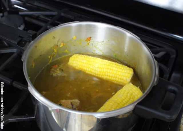 Foto de una sopa con mazorca dentro de una olla