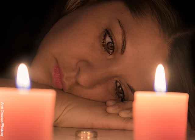 Foto de una mujer recostada sobre una mesa con velas encendidas