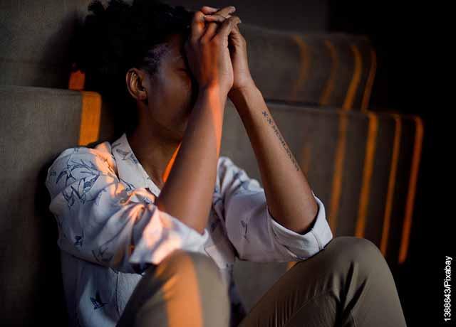 Foto de una mujer cubriendo su rostro sentada