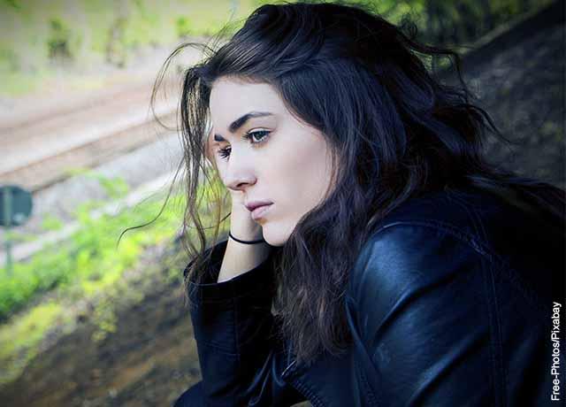 Foto de una mujer pensativa mirando por una ventana
