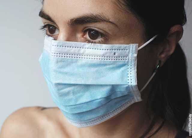 Foto de una mujer usando un tapabocas azul