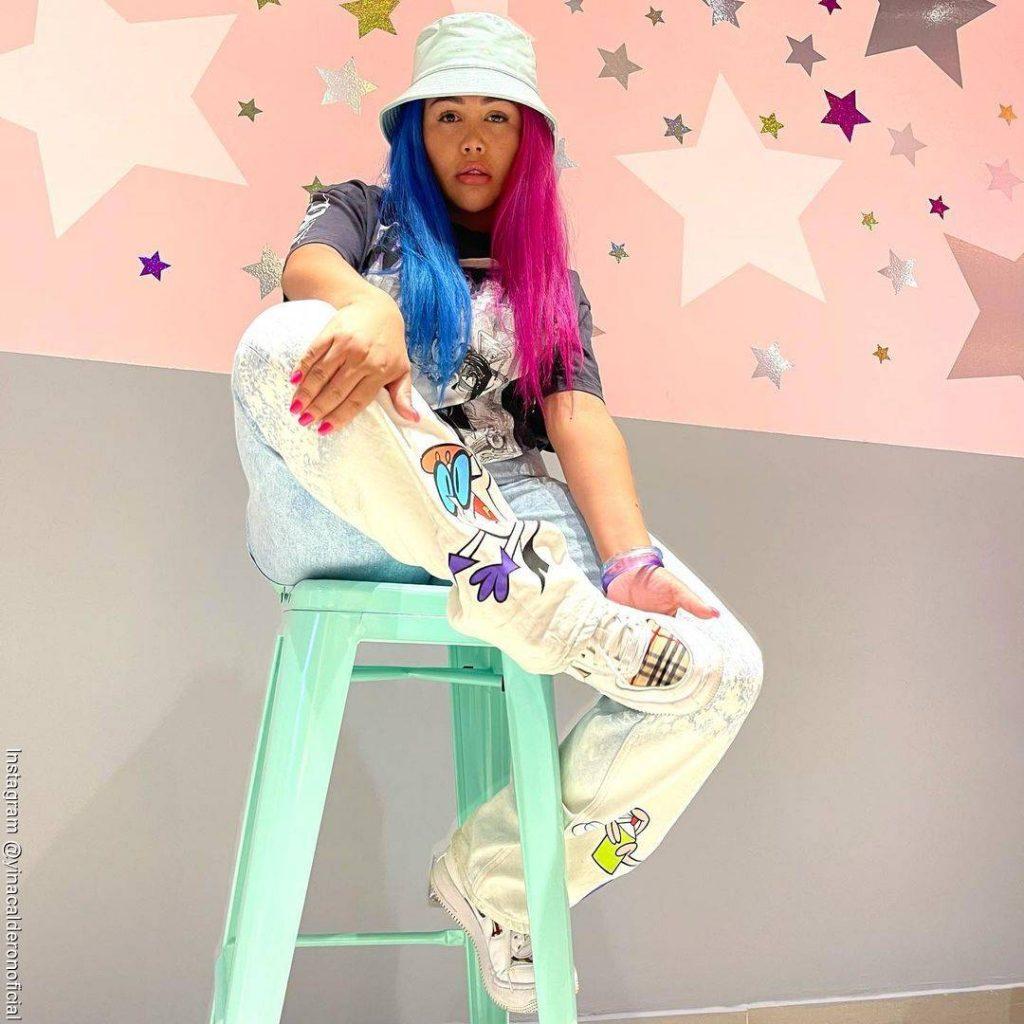 Foto de Yina Calderón sentada sobre una silla de barra de heladería