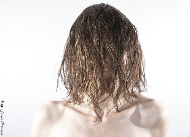 Foto de una mujer con el pelo sobre su rostro que muestra para qué sirve el agua de apio