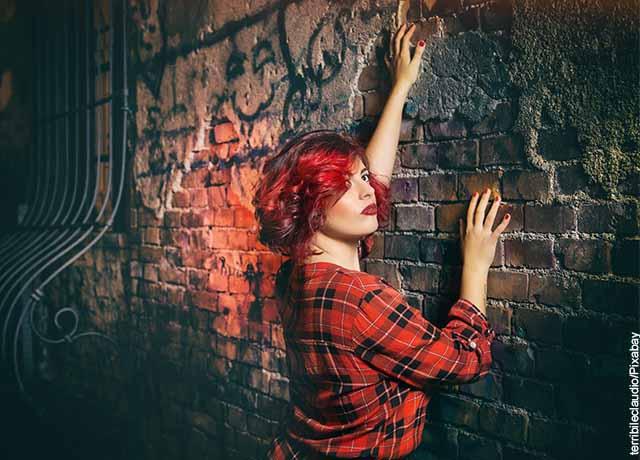 Foto de una mujer de cabello rojo agarrada a una pares que revela para qué sirve el amoniaco