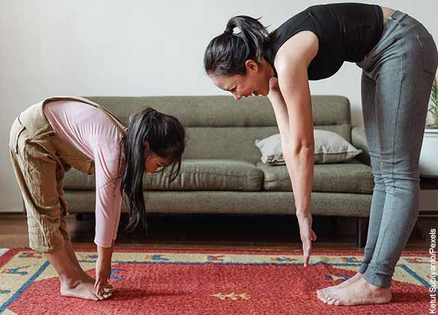 Foto de una mujer y una niña haciendo un ejercicio de calentamiento