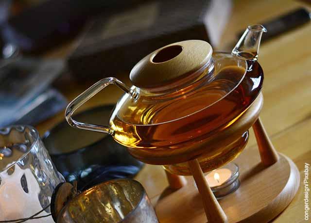 Foto de una tetera de vidrio sobre una mesa de madera