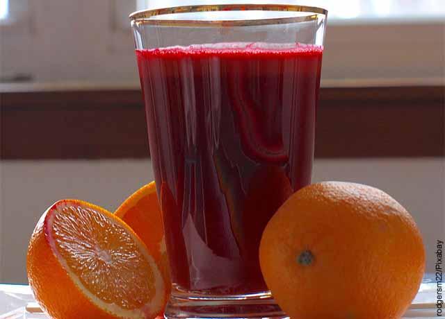 Foto de un vaso de jugo rojo con naranjas