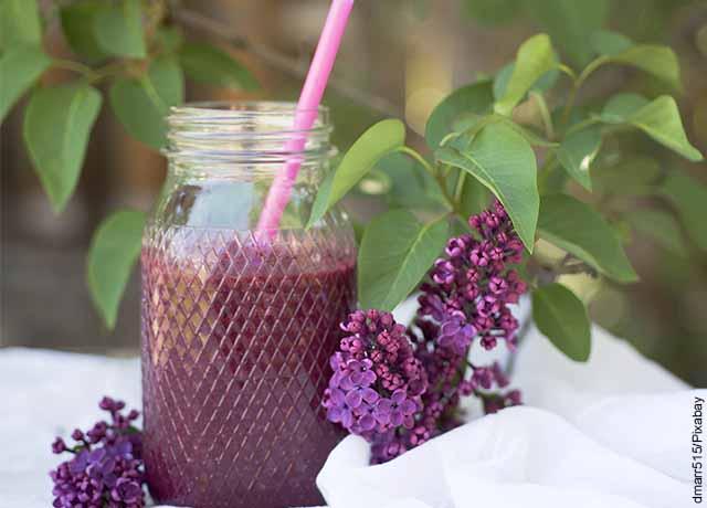 Foto de un recipiente de vidrio con jugo de remolacha adornada de flores