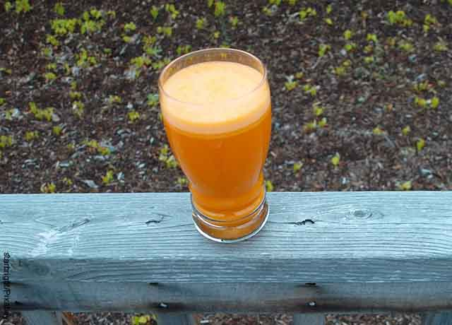 Foto de un vaso de una bebida de frutas sobre una tabla que muestra para qué sirve el jugo de zanahoria