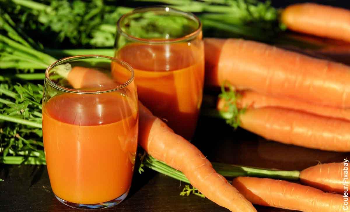 Foto de dos vasos de vidrio y varias zanahorias que muestra para qué sirve el jugo de zanahoria