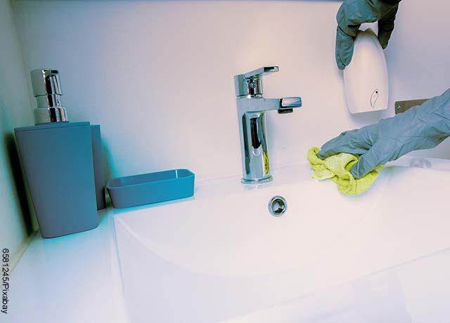 Foto de unas manos limpiando un lavamanos