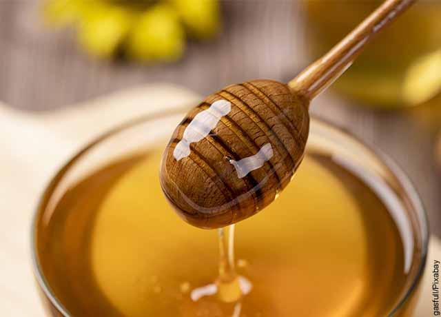 Foto de miel cayendo a un recipiente de vidrio