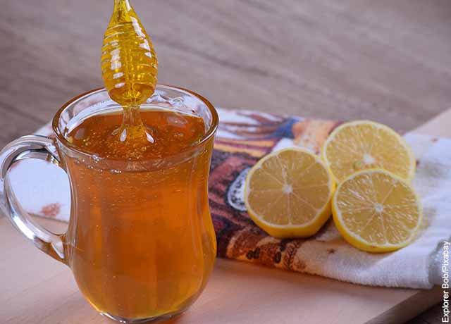 Foto de miel y aguapanela en un vaso junto con limones partidos