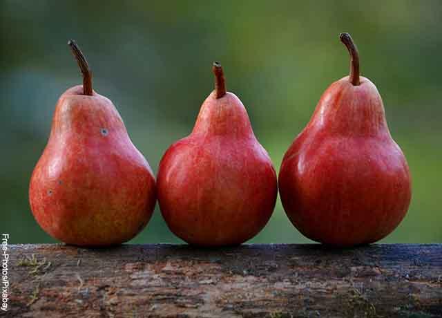 Foto de tres peras rojas sobre una madera