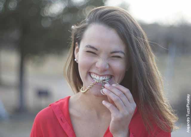 Foto de una mujer sonriendo mordiendo una cadena que muestra para qué sirve la vitamina A