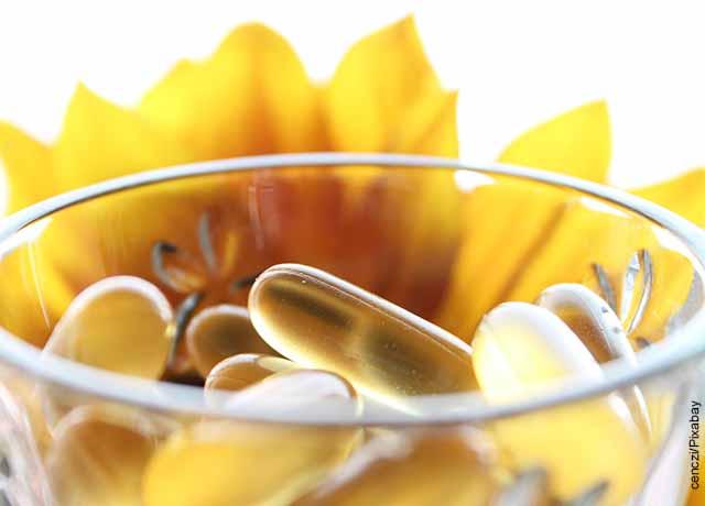 Foto de un recipiente con cápsulas amarillas y un girasol