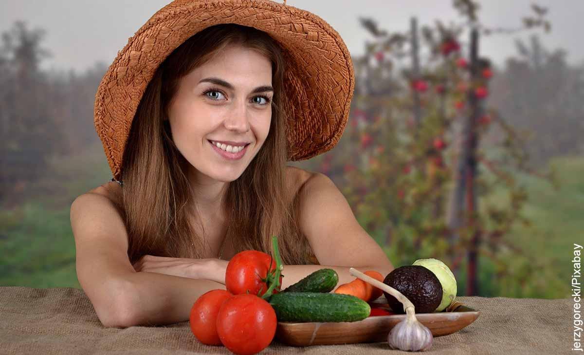 Foto de una mujer con sombrero al lado de algunas verduras que muestra para qué sirve la vitamina A