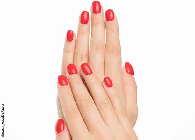 Foto de las manos de una mujer que muestra sus uñas rojas
