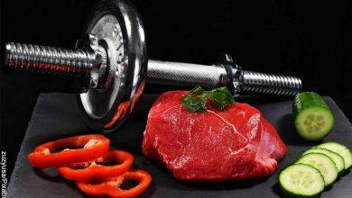 Foto de una pesa junto con un trozo de carne cruda, pimeones y pepino que revela qué comer antes de hacer ejercicio