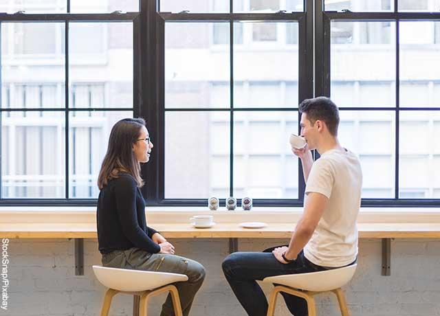 Foto de dos personas tomando un café que revela qué preguntas hacerle a un hombre
