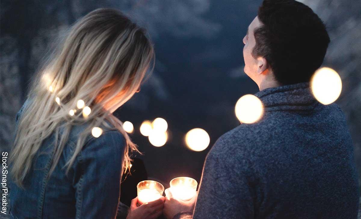 Foto de una pareja con velas en sus manos que muestra qué preguntas hacerle a un hombre
