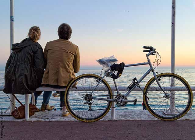 Foto de una pareja sentada viendo hacia el mar que muestra qué preguntas hacerle a una mujer