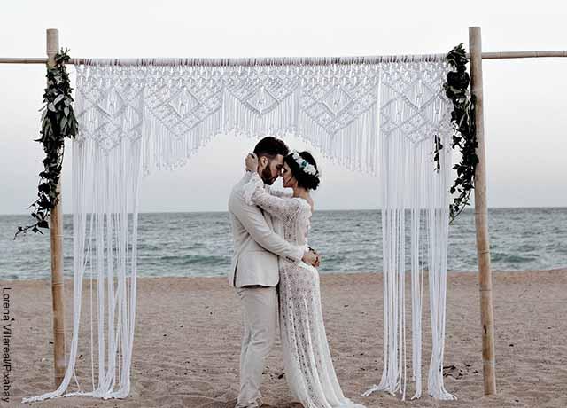 Foto de una pareja de recién casados besándose en la playa