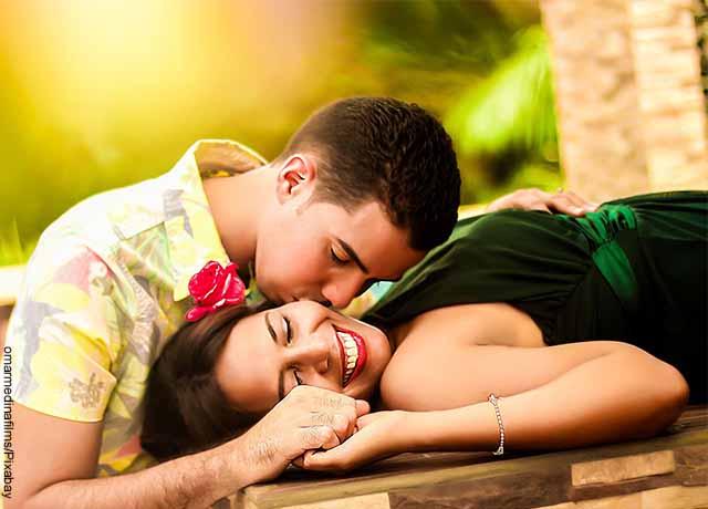 Foto de un hombre dándole un beso a su mujer mientras sonríe