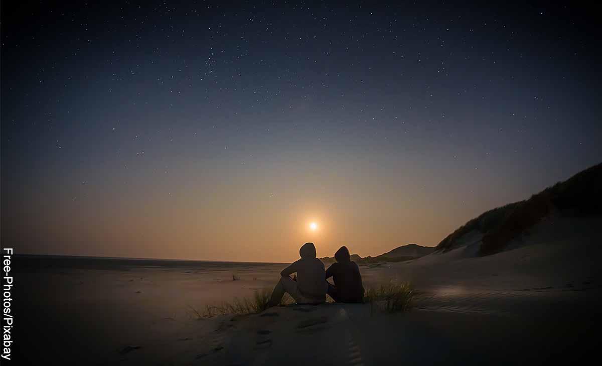 Foto de dos personas sentadas en la playa viendo el atardecer que muestra qué preguntas hacerle a una mujer