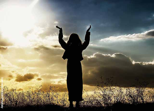 Foto de una mujer rezando con las manos hacia el cielo