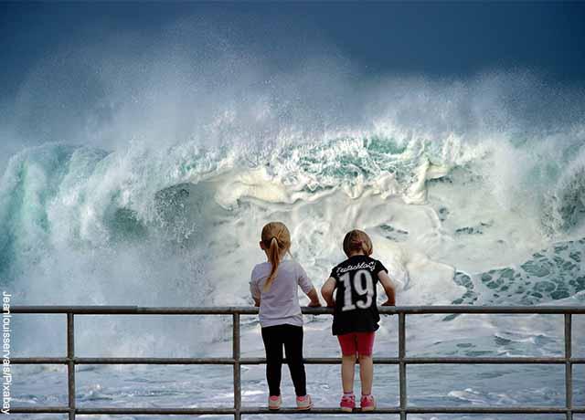 Foto de dos niños sobre un puente y olas de mar gigantes que muestra qué significa soñar con tsunami