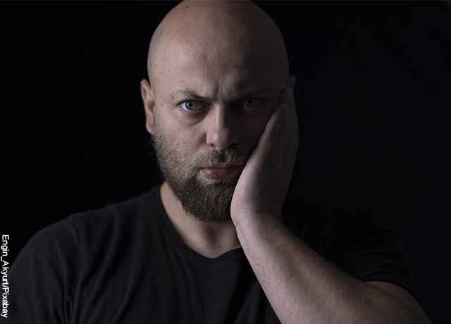 Foto de un hombre tomando su rostro con aparente dolor