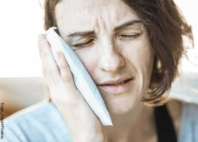 Foto de una mujer muy adolorida poniendo una compresa en su cara