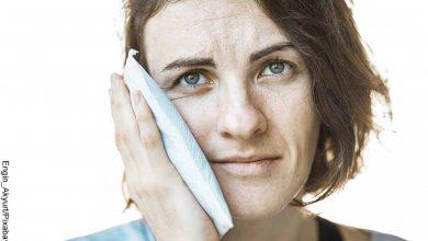 Foto de una mujer poniendo un paño en su cara que muestra qué sirve para el dolor de muela