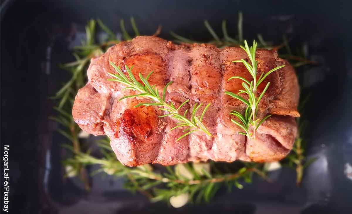 Foto de un rollo de carne con romero en un recipiente que muestra la receta de rollo con carne