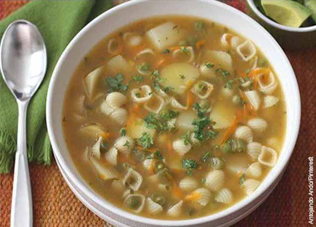 Foto de una sopa de pasta y verduras con aguacate