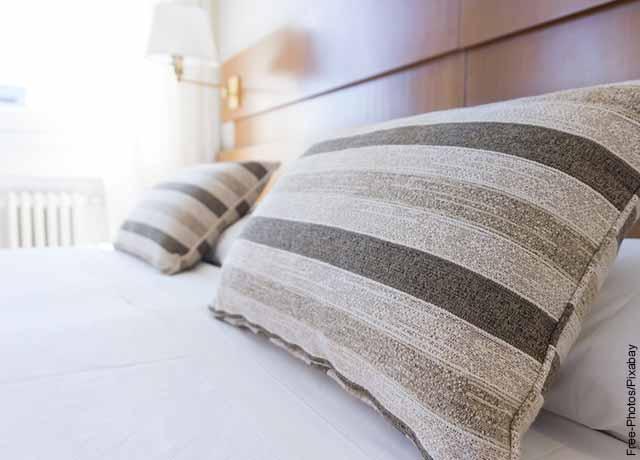 Foto de una cama da madera con almohadas