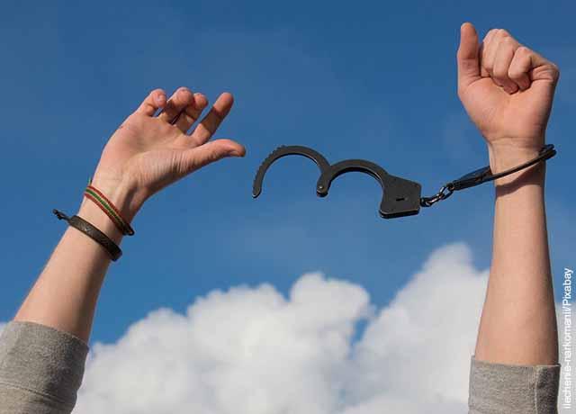 Foto de unas manos liberándose de unas esposas que muestra lo que es soñar con cárcel