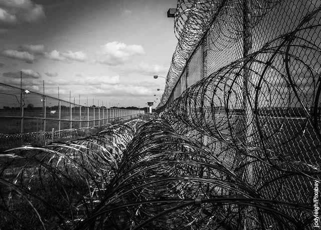 Foto de las rejas y alambrado de una prisión