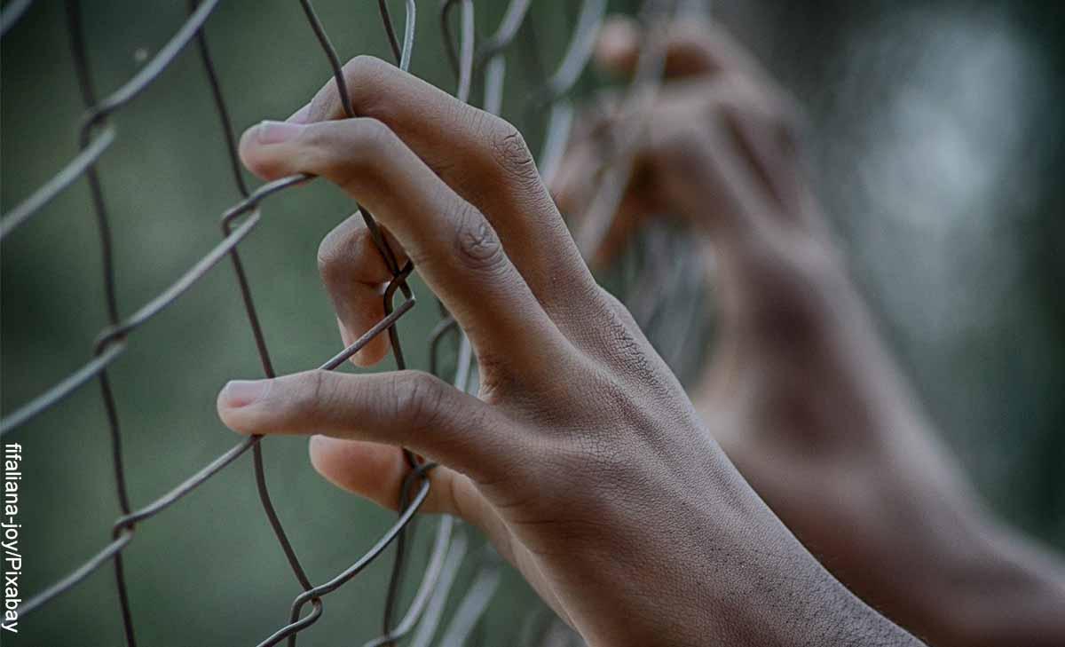 Foto de unas manos sosteniendo una reja que muestra lo que es soñar con cárcel