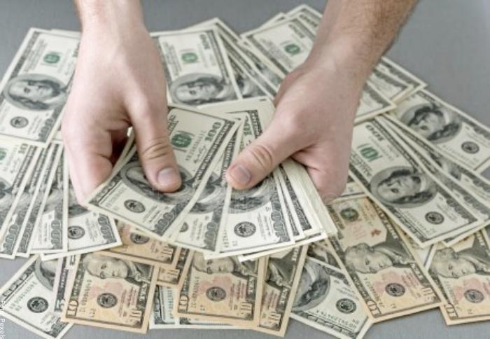 Foto de una persona con dólares en la mano