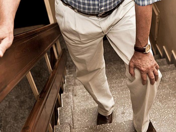 Foto de hombre subiendo escaleras con dificultad