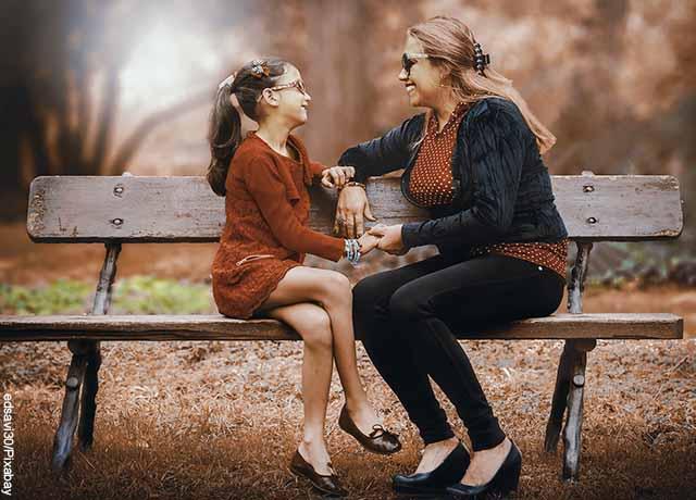 Foro de una mujer con su hija sentadas en una banca