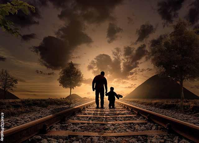 Foto de un hombre caminando con un niño por el ferrocarril que muestra lo que es soñar con familiares