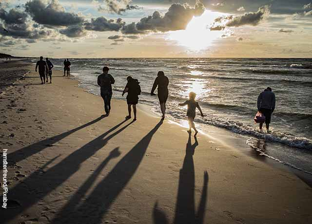 Foto de varias personas caminando por la playa